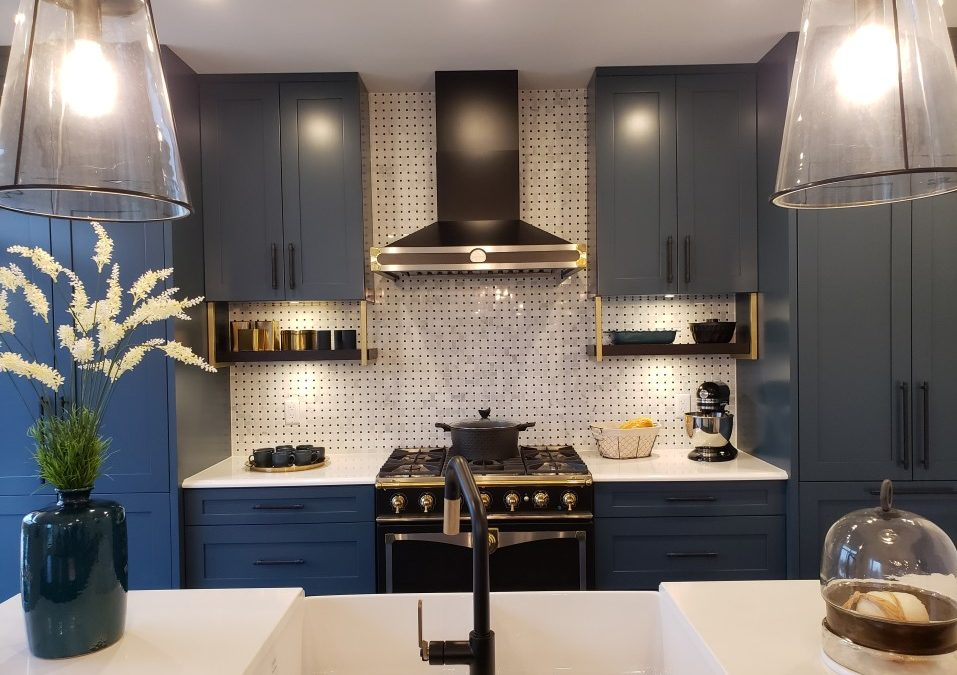 A modern kitchen with white countertops and blue-painted cabinets.