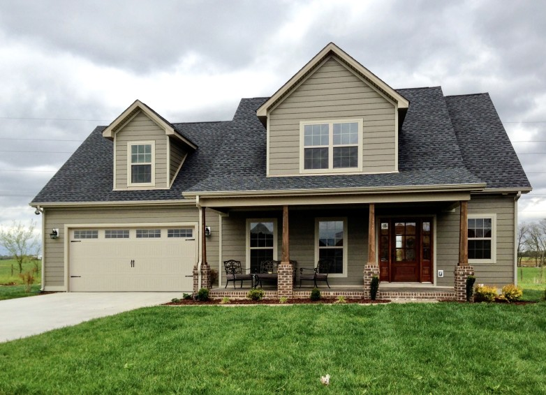 new construction house with dark colored roof, brick accents, and neutral toned siding and ranch-style garage door