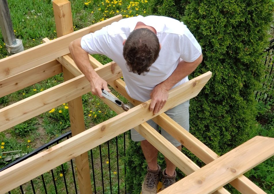 Above view of a man hammering a nail into a piece of wood building a pergola at his home with greenery and trees in the background